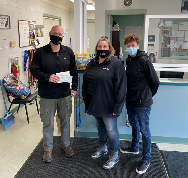 Petland Athens, OH General Manager Sally Jo Kuntz and Petland District Manager Nicole Soule present a $1,000 check to Ryan Gillette with the Athens County Dog Shelter. Gillette said the funds will be put into their sick and injured fund to offset the cost of medical treatments.