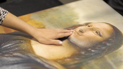 A visitor explores the surface of a tactile image of 'The Mona Lisa'.