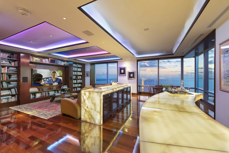 """The residence's lounge includes custom theater seating, in addition to ample wine storage and an adjacent, """"floating"""" wet bar, both of which feature illuminated onyx countertops. Endless views of the Atlantic Ocean provide the backdrop. MiamiLuxuryAuction.com."""