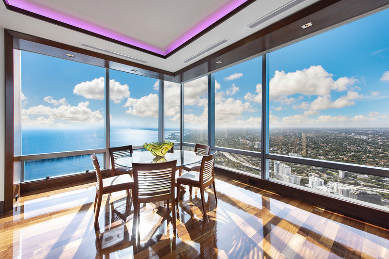 A charming breakfast area is located just off of the entertainment lounge. Walls of floor-to-ceiling windows offer inspiring views of the sparkling Atlantic and Miami coastline. MiamiLuxuryAuction.com.
