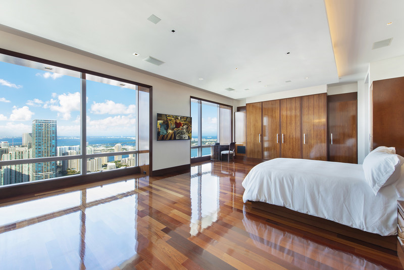 The spacious master suite boasts custom woodwork, a private balcony, expansive walk-in closets for him-and-her and grand views of downtown Miami and its waterways. Visit MiamiLuxuryAuction.com.