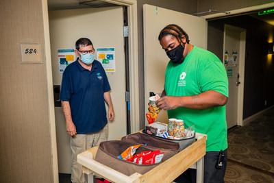 Paul, cliente de Chrysalis y funcionario de National Health Foundation, sirve meriendas a los huéspedes del centro del Proyecto Roomkey de NHF. (PRNewsfoto/National Health Foundation)