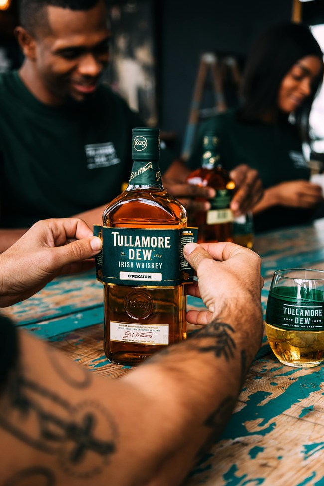 Person places a label of Tullamore on bottle.