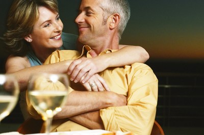 Relaxed couple sitting enjoying a glass of wine together share a special moment of affection and love