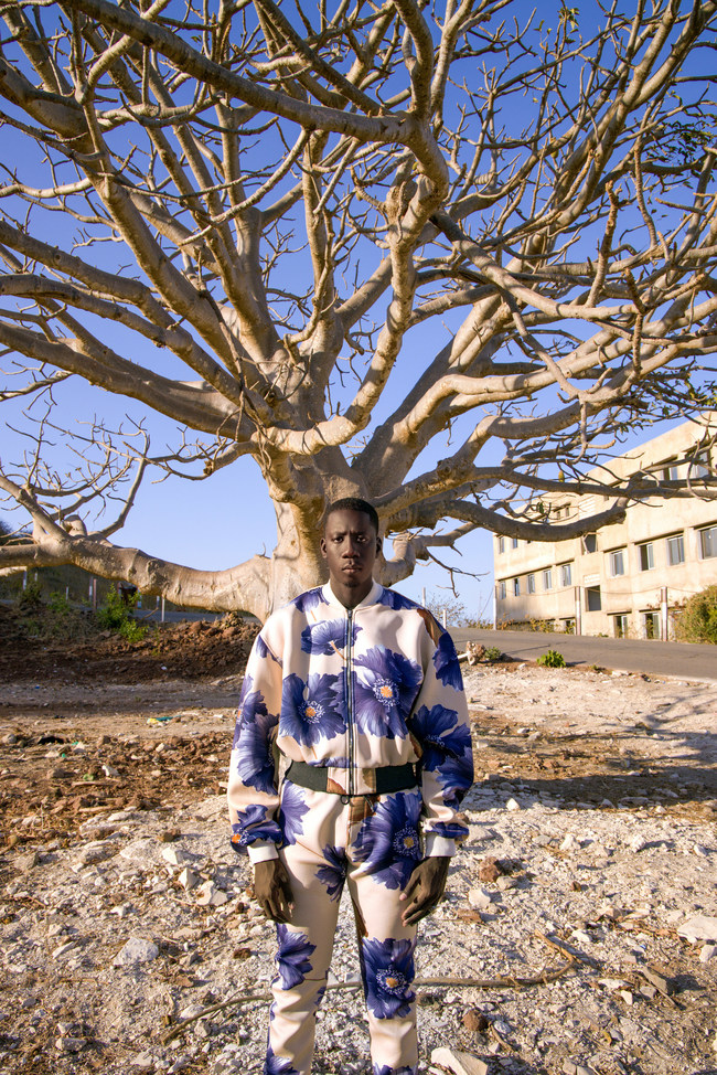 Bamba Ndiaye Posing In Front Of The Mysterious Baobab Tree Also Known As The Tree Of Life. Photography by Djibril Drame.