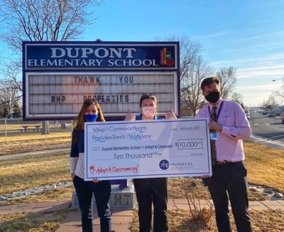 Dupont Elementary Assistant Principal Kelly Hynes and Principal Brian Clark accept the $10,000 donation from Mindy Love, Community Manager of Wikiup, Commerce Heights and Shady Lane communities on behalf of RHP Properties.