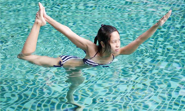 Asian woman doing aqua yoga pose in pool