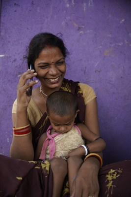 A woman listens to an mMitra call on her phone in Nala Sopara, Mumbai. Google AI is supporting ARMMAN in designing an AI technology solution that identifies women at high risk of dropping out of the program, which helps ARMMAN to personalise interventions for an improved engagement with mMitra