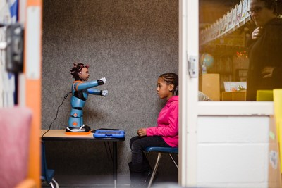 A student with Autism Spectrum Disorder is seen here working with Carver, one of four robot models developed by RoboKind.
