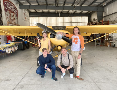 Foster's Lab team next to banner towing plane.
