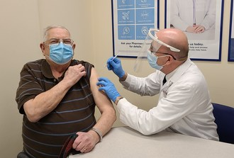 Shoppers Drug Mart Associate Owner Tony Alm gives the store's first COVID-19 vaccine to Eugene Bochon in Edmonton, AB. (CNW Group/Loblaw Companies Limited)