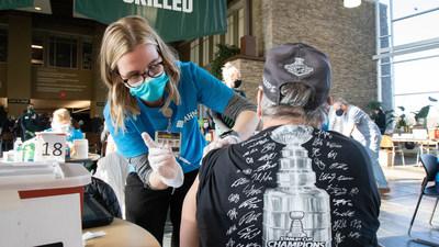 AHN clinician administers vaccine shot.