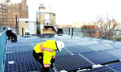 Workers installing solar panels at Carver Houses, a New York City Housing Authority development in northern Manhattan. Photo credit: Accord Power Inc.
