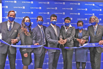 Ribbon cutting of first United flight from JFK to SFO with David Kinzelman and Ankit Gupta surrounded by flight crew and employees.
