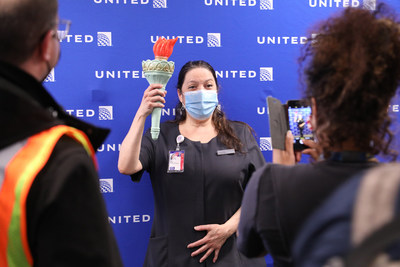 Esther Paz, United Customer Service agent poses with the torch carried cross country on the inaugural flight.