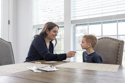 在进行Abbott Binaxnow™Covid-19自检之前,母亲使用浅鼻拭子擦拭她儿子的鼻孔。该测试将在主要的美国零售商处于柜台上方提供,不需要处方。(Prnewsfoto / Abbott)