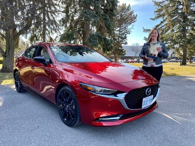 AJAC President Stephanie Wallcraft holds the Canadian Car of the Year award next to the 2021 Mazda3 Turbo. (CNW Group/Mazda Canada Inc.)