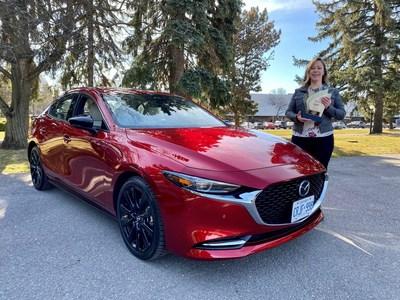 Stephanie Wallcraft, présidente de l'AJAC, présente le prix de la Voiture canadienne de l'année aux côtés du Mazda3 Turbo 2021. (Groupe CNW/Mazda Canada Inc.)