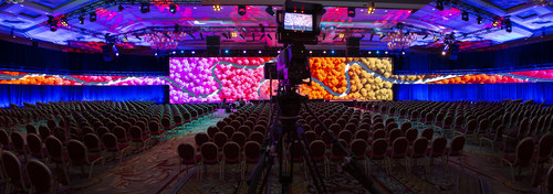 """Signature Production Group – a production technology provider for live meetings and events – is increasing their inventory of high-resolution THOR LED tiles powered by Brompton Technology.  The LED wall in this photo is over 100' wide and features """"ribbons"""" that wrap around the entire audience.  Signature Production Group uses a combination of Disguise One VX4 Media Servers and Barco Event Master E2's for managing the screen content."""