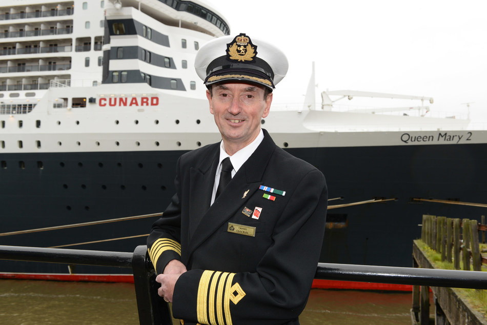 Cunard Captain Christopher Wells standing in front of flagship Queen Mary 2. As Wells embarked on his retirement this week, he was awarded the rank of Commodore in recognition of his 20 year career with the brand (April 2021)
