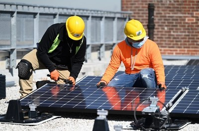 Two New York City Housing Authority residents who have gotten apprenticeships as solar installers under a Con Edison project. The 12 apprentices are placing panels on three NYCHA developments. The power will be available to low- and moderate-income customers on a discounted basis.