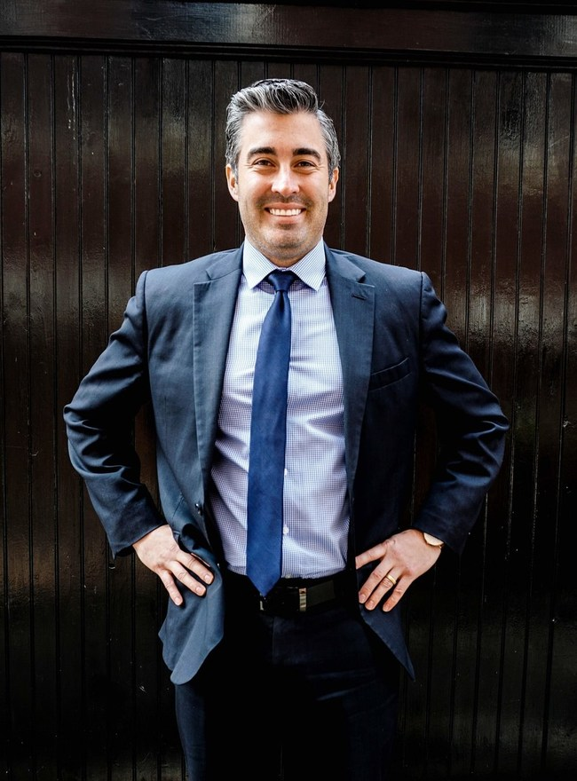 Paul Toland Law, Criminal Defense Attorney in Boston Smiling with Suit on Hands on Hips
