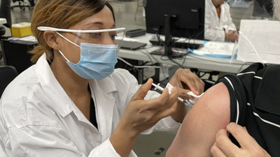 Health worker in a mask and face shield administers a needle to a seated person's shoulder (CNW Group/Unifor)