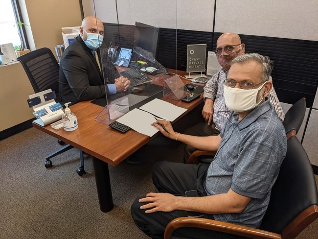 Photo: Arun Kankani, President, Sewa International, foreground, and Yagnesh Patel, Compliance Manager, to his right, wiring the money from a bank in Houston to purchase 2,184 Oxygen-concentrators.