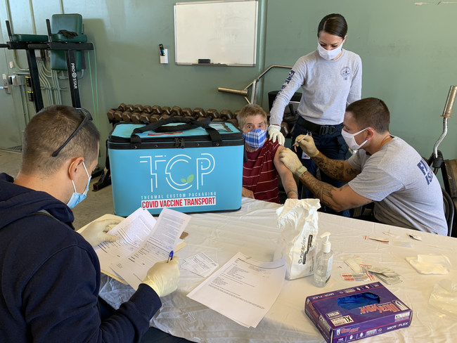 Thermal Custom Packaging Totes Maintaining COVID Vaccines Refrigerated 2-8 Centigrade During a Vaccination Clinic.