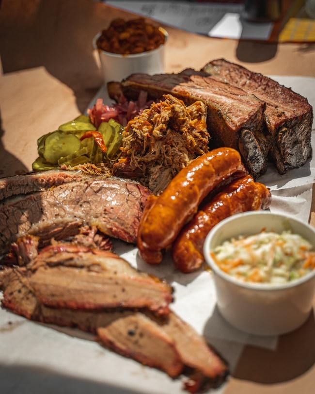 Signature #jigglymeatdishes include Kalman's Salt & Pepper Brisket, Carolina Pulled Pork, Chipotle Cider Glazed Drumsticks, Pork Spare Ribs, housemade Hatch Chile and Cheddar Hot Links, and Texas Sausages.