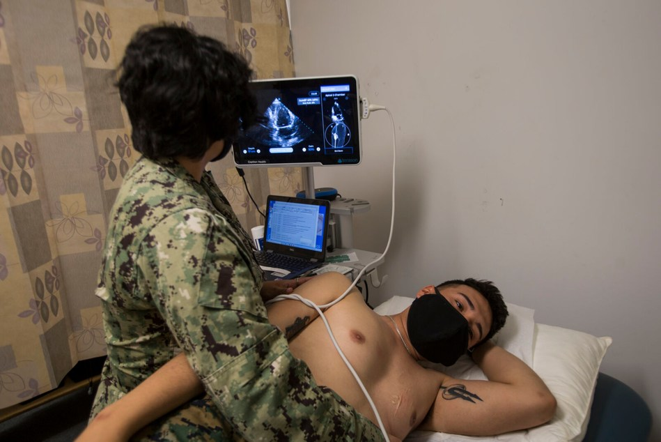 U.S. Navy Hospital Corpsman 3rd Class Victoria Diaz, with the Naval Medical Research Center, conducts an ultrasound of a Marine participant using Caption AI with the COVID-19 Health Action Response for Marines (CHARM) study on Camp Johnson. (U.S. Marine Corps photo by Sgt. Jesus Sepulveda Torres)