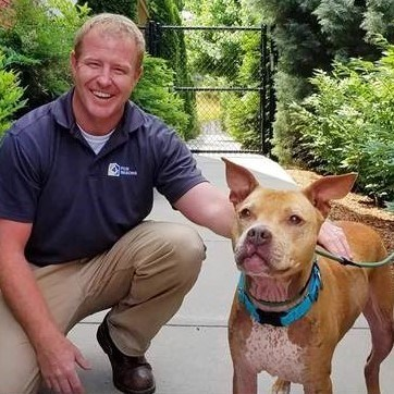 Pictured is Four Seasons Plumbing owner Max Rose kneeling next to Mable. Four Seasons Plumbing encourages residents to adopt a pet in recognition of National Pet Month in May.