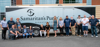 Volunteers pose after helping to load thousands of medical supplies and durable medical equipment into two trailers at large donation event.