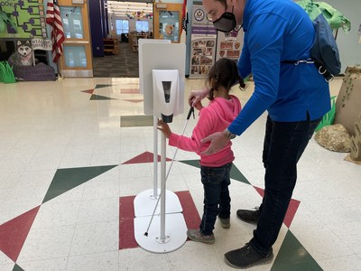 In an elementary school hallway, an orientation and mobility specialist wearing a mask assists a blind student to locate and use a hand sanitizer station after she locates it with her white cane.
