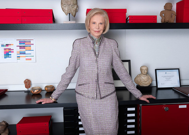 A photograph of Marica Vilcek in her office. Marica has chin-length blonde hair and wears a lavender suit.