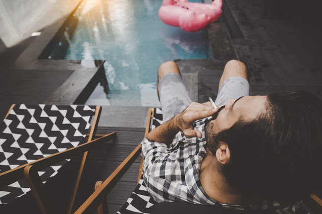Man smoking cannabis by pool