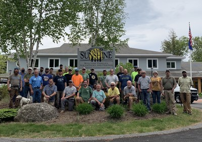 Pictured here are volunteers from the DIY Network hit show Maine Cabin Masters and crews from Landry/French Construction who came together to help replace 68 windows in Camp Sunshine at Sebago Lake's Viterbi Family Activity Center.