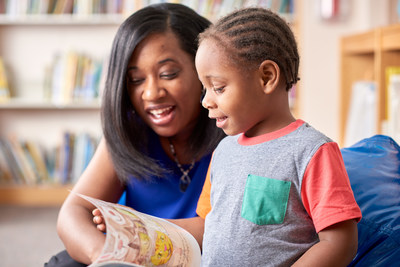 Tiana Rollinson Henry, a community engagement specialist at Cincinnati Children's, shares a book with a child.
