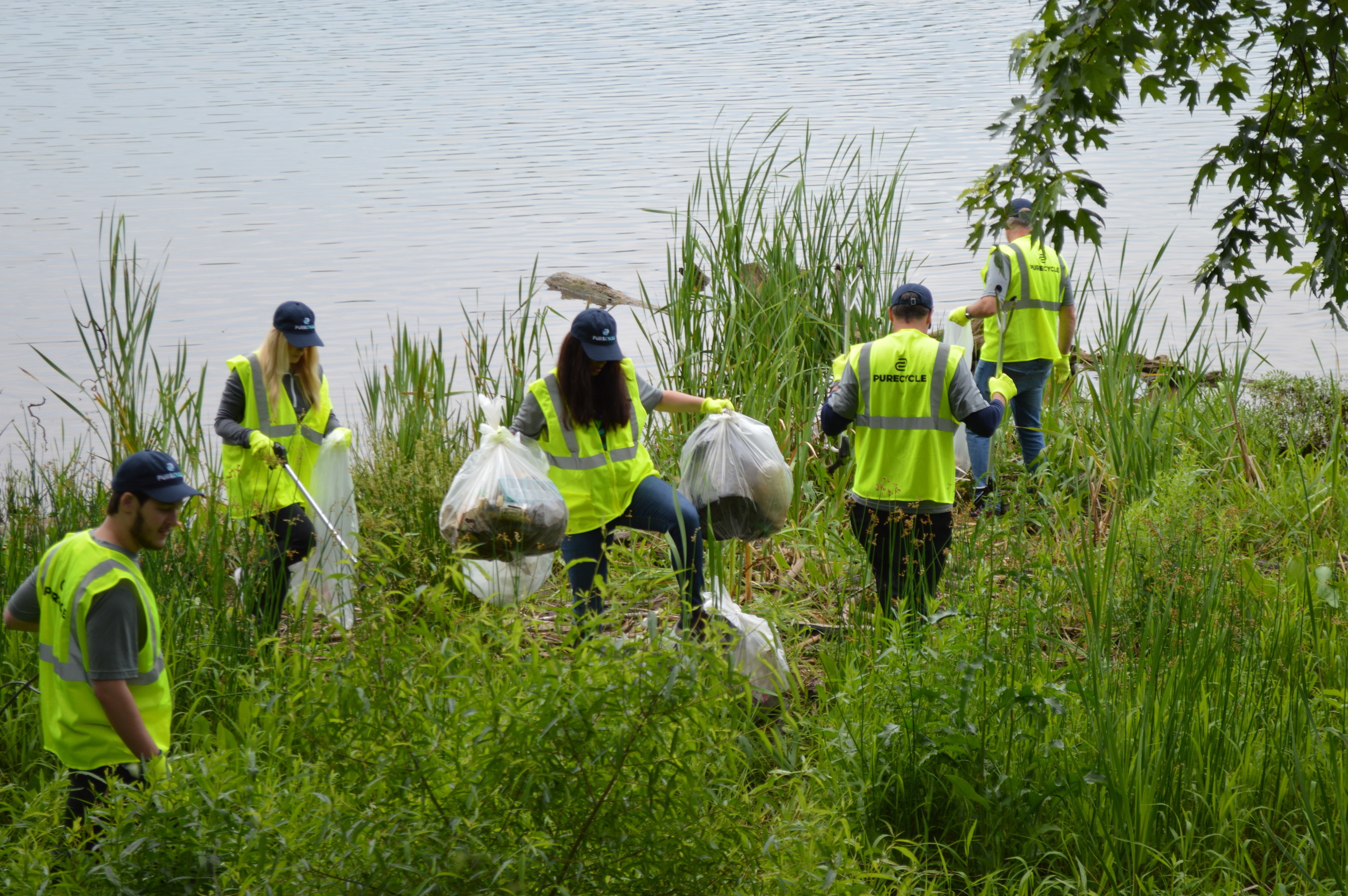 The Pure Planet Day team collects plastic waste along the Ohio river bank and County Road 1A in Ironton near PureCycle's recycling facilities.