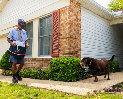 Annapolis, MD letter carrier Thomas Tyler takes a protective stance against an approaching dog.