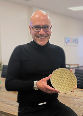 Cem Basceri, QROMIS president and CEO, displays a 200 mm diameter 650V, E-mode gallium nitride (GaN) discrete power device wafer on a QST® (QROMIS Substrate Technology) substrate. (Courtesy photo by QROMIS)