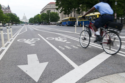 Washington DC, USA - June 11, 2012: A bicyclist peddles down Pennsylvania Avenue in downtown Washington using cycling lanes established in the middle of the street. The U.S. Capitol Building and other traffic is visible in the background.