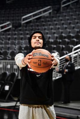Trae Young, membro da equipe consultiva da Wilson e armador principal do Atlanta Hawks, segura a nova bola de jogo oficial da NBA.