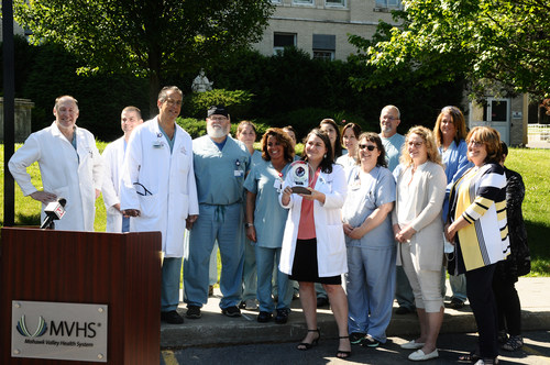 Members of the Mohawk Valley Health System (MVHS) cardiac team hold their award from the American College of Cardiology (ACC) this morning in front of St. Elizabeth Medical Center. MVHS is the first hospital in the state and one of 36 nationally to be awarded the ACC's highest accreditation of HeartCARE™ Center: National Distinction of Excellence. Members of the team were on hand to announce the prestigious award, which is the culmination of more than two years of planning and on site testing.