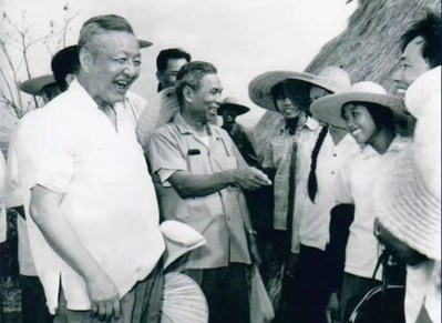 File photo of Xi Zhongxun (L) talking to people in Guangdong Province, China.