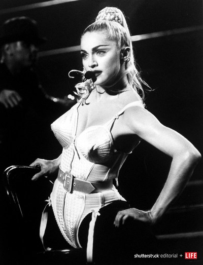 """Singer Madonna wearing a pointed-bust corset by fashion designer Jean-Paul Gaultier while performing during her """"Blonde Ambition"""" concert at Nassau Coliseum in 1990. Photo credit: DMI/The LIFE Picture Collection/Shutterstock."""