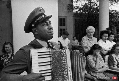FDR'S WARM SPRINGS FUNERAL - Navy CPO Graham Jackson with tears of grief streaming down his cheeks as he plays 'Goin' Home' on the accordion, while President Franklin D. Roosevelt's body is carried from the Warm Springs Foundation where he died suddenly on April 12, 1945 of a stroke. Photo credit: Ed Clark/The LIFE Picture Collection/Shutterstock.