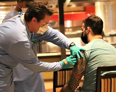 Seminole Tribe of Florida Fire Rescue Paramedic Kristoffer Durthaler vaccinates Seminole Hard Rock Tampa team member Nicolas Diaz-Granados.