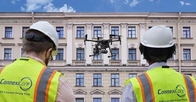 Drone pilots inspecting a building façade