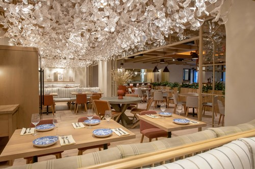 Serena Pastificio's dining room, featuring warm wood accents + a stunning hanging art installation